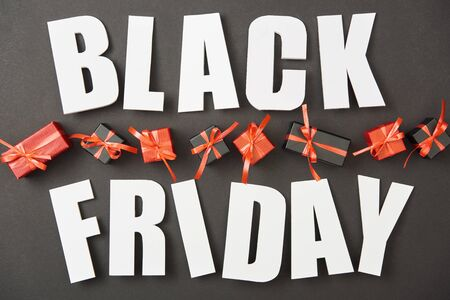 top view of black friday white lettering near presents on black background