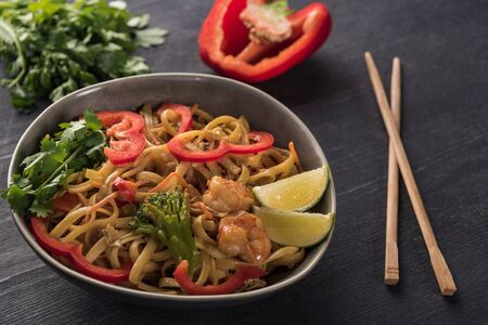 tasty spicy thai noodles with shrimps near chopsticks on wooden grey surface