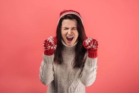 angry woman in red gloves screaming on pink
