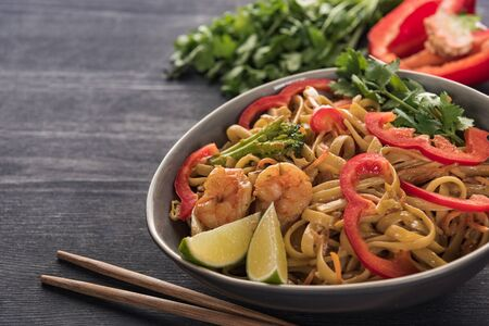 delicious spicy thai noodles with shrimps near chopsticks on wooden grey surface