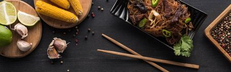 top view of noodles near chopsticks, garlic and corn on wooden grey surface, panoramic shot