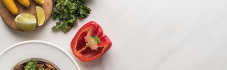 top view of delicious thai noodles near bell pepper, parsley and corn on marble grey surface, panoramic shot