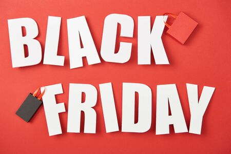 top view of black friday white lettering with shopping bags on red background