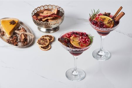 christmas cocktails with orange, pomegranate, cinnamon, apple pie and dry apples