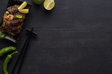 top view of tasty spicy meat thai noodles near chopsticks on wooden grey surface with copy space