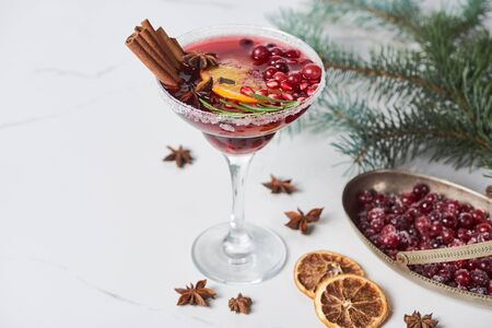 christmas cocktail with orange, pomegranate, cinnamon and frozen cranberry