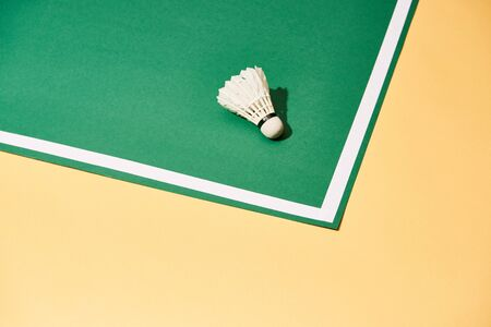 Badminton shuttlecock on yellow and green surface with white line Stock Photo
