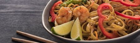 close up view of thai noodles with shrimps near chopsticks on wooden grey surface, panoramic shot