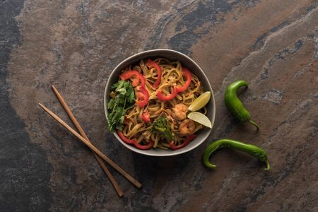 top view of tasty spicy thai noodles with shrimps near chopsticks on stone surface