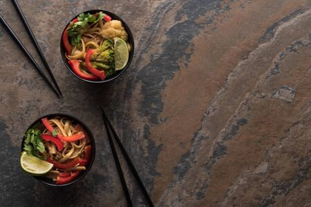 top view of tasty spicy thai noodles with chopsticks on stone surface Stock Photo