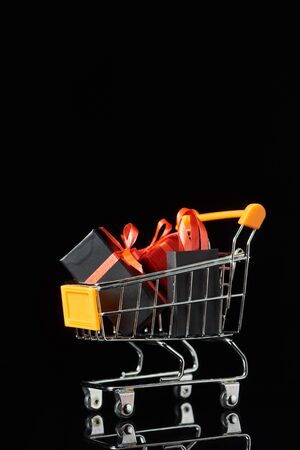small gifts and shopping bag in decorative trolley isolated on black 스톡 콘텐츠