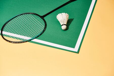 Metal badminton racket and shuttlecock on playground with line and yellow surface Stock Photo