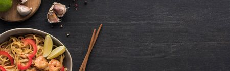 top view of tasty spicy thai noodles with garlic and shrimps near chopsticks on wooden grey surface, panoramic shot