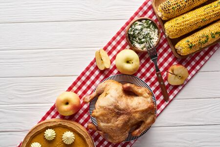 top view of pumpkin pie, turkey and vegetables served at white wooden table on red plaid napkin for Thanksgiving dinner