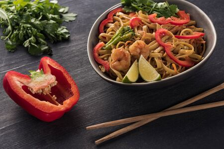 selective focus of tasty spicy seafood thai noodles near chopsticks, paprika and parsley on wooden grey surface