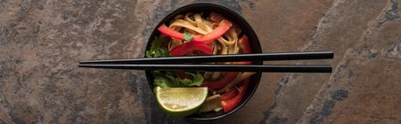 top view of thai noodles and chopsticks on stone surface, panoramic shot Stock Photo