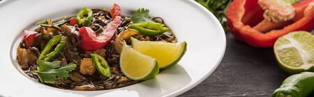 close up view of meat thai noodles near ingredients on wooden grey surface, panoramic shot Stock Photo