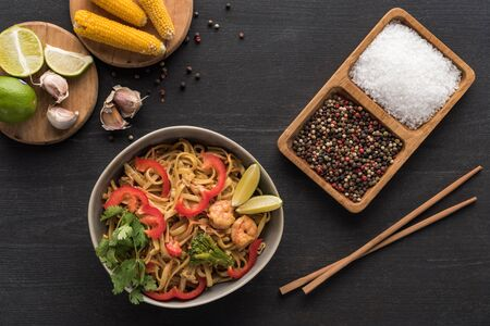 top view of delicious spicy thai noodles with shrimps near chopsticks, seasoning, lime and corn on wooden grey surface Stock Photo