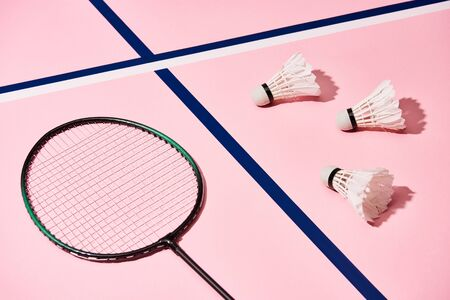 Badminton racket and shuttlecocks on pink background with blue lines