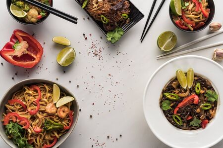 top view of delicious spicy thai noodles near chopsticks and ingredients on marble grey surface Stock Photo