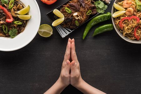 cropped view of praying hands near delicious spicy thai noodles on wooden grey surface