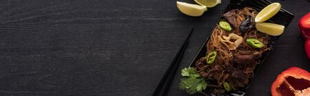 top view of meat thai noodles near chopsticks, lime and paprika on wooden grey surface, panoramic shot Stock Photo