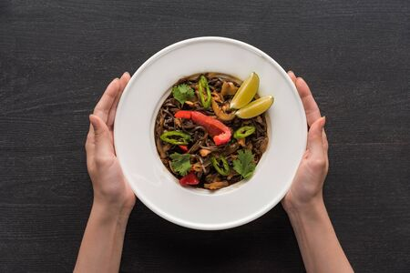 cropped view of woman holding plate with tasty spicy thai noodles on wooden grey surface
