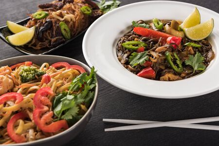 delicious spicy thai noodles near chopsticks on wooden grey surface
