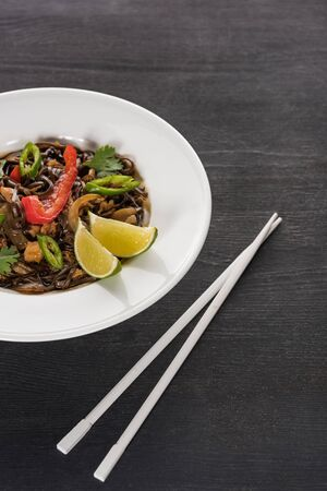 vegetable delicious spicy thai noodles near chopsticks on wooden grey surface Stock Photo