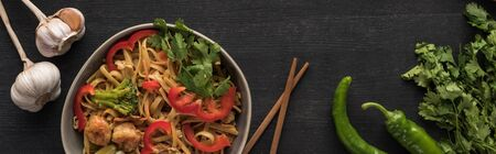 top view of tasty spicy thai noodles with garlic, parsley, jalapenos near chopsticks on wooden grey surface, panoramic shot