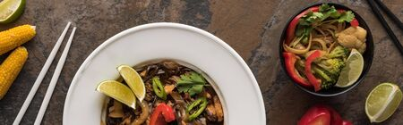 top view of thai noodles with vegetables and meat near chopsticks, panoramic shot, panoramic shot
