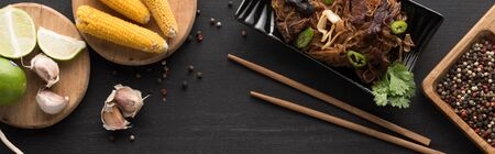 top view of tasty spicy thai noodles near chopsticks and fresh ingredients on wooden grey surface, panoramic shot