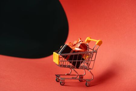 decorative gifts in small shopping cart on red paper isolated on black