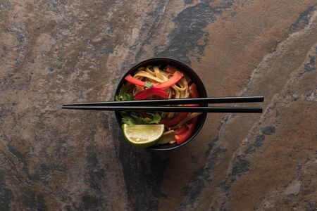 top view of delicious spicy thai noodles with chopsticks in bowl on stone surface Banque d'images