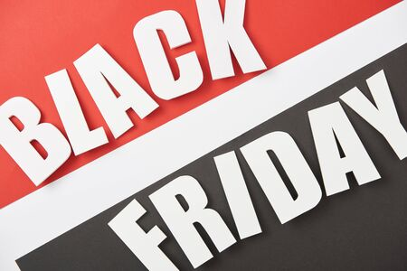 top view of black friday lettering on black, white and red background