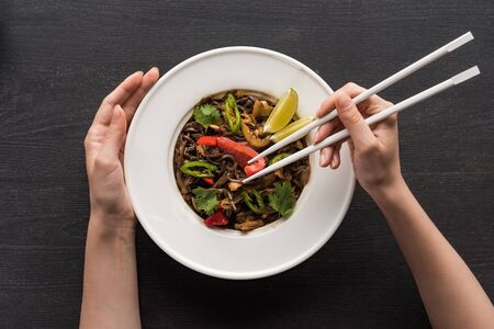 cropped view of woman holding chopsticks near plate with tasty spicy thai noodles on wooden grey surface Stock Photo