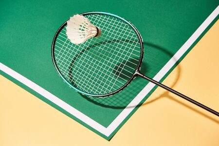 Badminton racket and shuttlecock on green and yellow surface with line