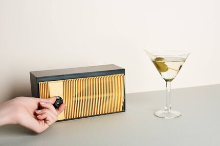 Cropped view of woman adjusting volume of retro radio with martini cocktail beside 写真素材