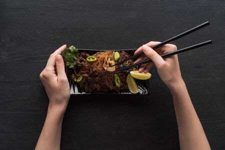 cropped view of woman eating delicious spicy thai noodles with chopsticks on wooden grey surface