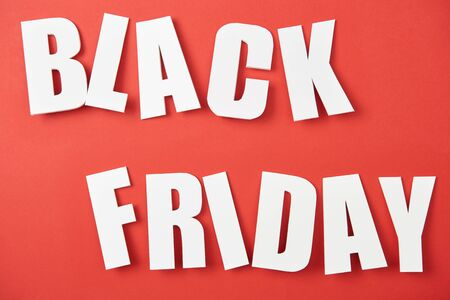 top view of black friday white lettering on red background