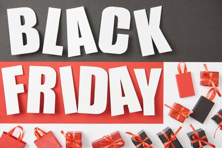 top view of black friday lettering near presents on black, red and white background