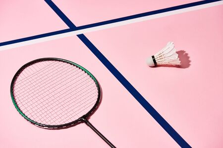 Badminton racket and shuttlecock on pink background with blue lines