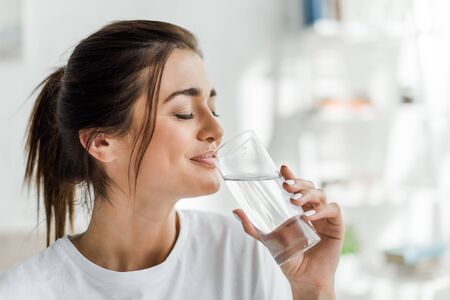 smiling girl holding drinking water from glass in the morning