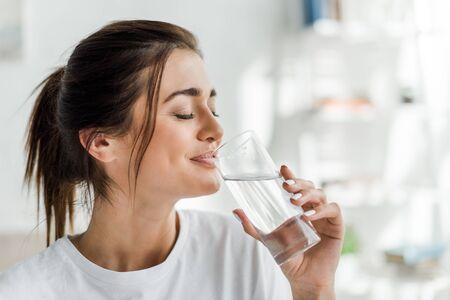 lachend meisje dat 's ochtends drinkwater uit glas vasthoudt
