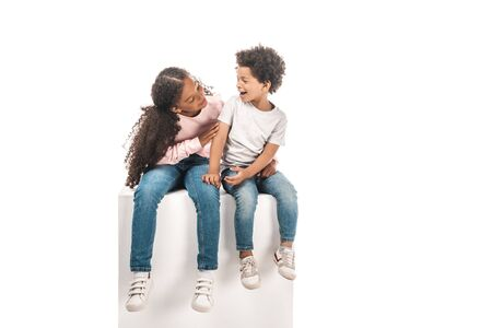 cute african american sister looking at adorable brother while sitting on white cube together isolated on white