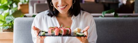 panoramic shot of happy woman holding plate with tasty sushi 写真素材