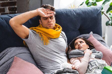 sick girlfriend with napkin and handsome boyfriend with high temperature