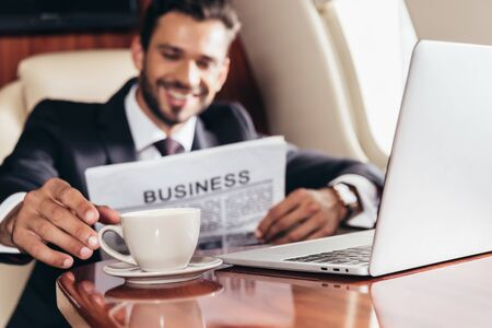 selective focus of smiling businessman in suit with newspaper taking cup in private plane