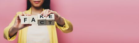 cropped view of asian woman holding wooden cubes with fake and fact lettering isolated on pink, panoramic shot