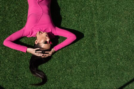 top view of attractive woman in dress and sunglasses posing and lying on grass outside Zdjęcie Seryjne